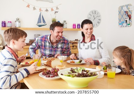 Family Eating Lunch At Kitchen Table - stock photo