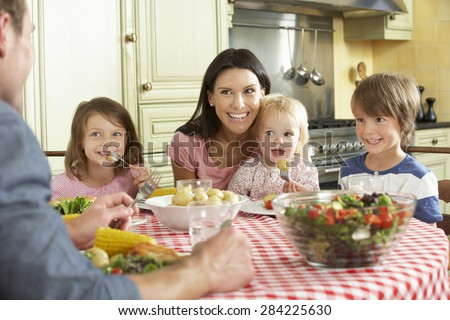 Family Eating Meal Together In Kitchen - stock photo