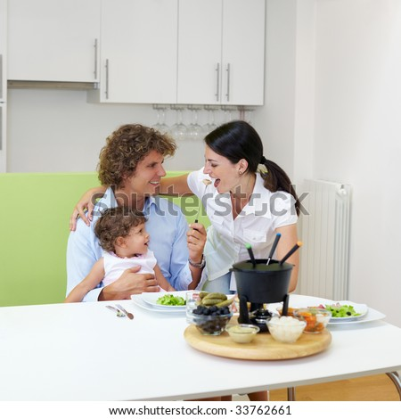 family eating meat fondue at home. Copy space - stock photo