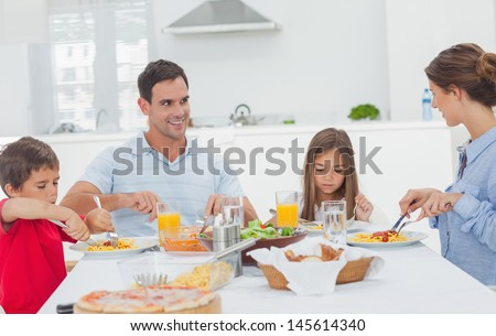 Family eating pasta with sauce for the dinner - stock photo