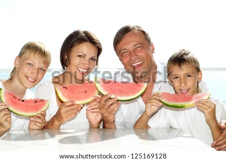 family eating watermelon in the background of the sea - stock photo