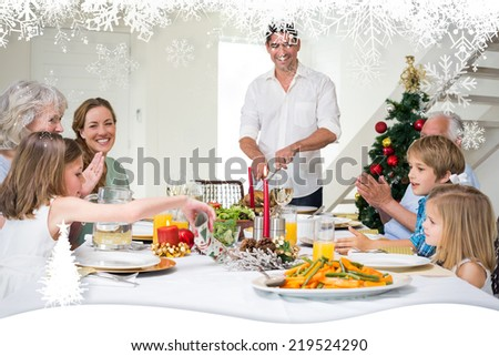 Family enjoying Christmas meal at dining table against fir tree forest and snowflakes - stock photo