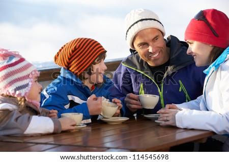 Family Enjoying Hot Drink In Cafe At Ski Resort - stock photo