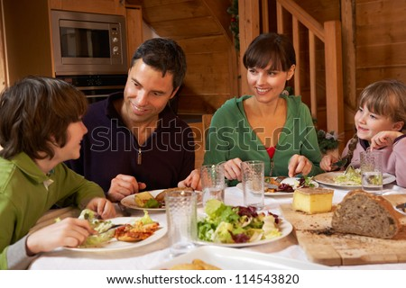 Family Enjoying Meal In Alpine Chalet Together - stock photo