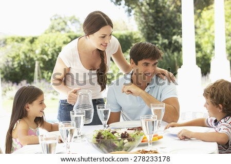 Family Enjoying Outdoor Meal In Garden Together