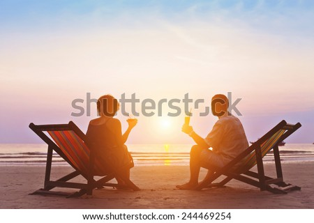 family enjoying romantic sunset on the beach - stock photo