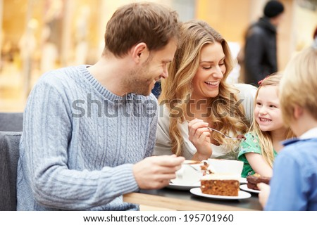 Family Enjoying Snack In Cafe Together - stock photo