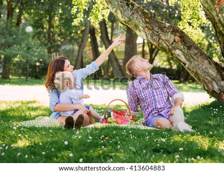 Family enjoying their leisure having a picnic in the park.