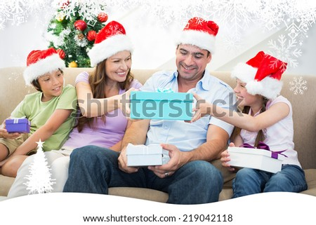 Family exchanging Christmas gifts against fir tree forest and snowflakes