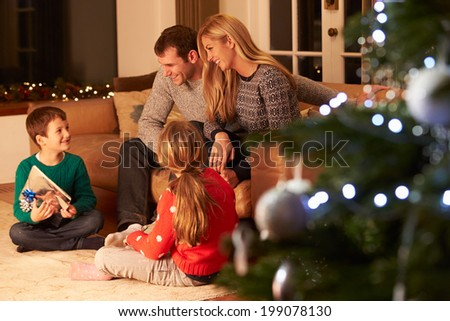 Family Exchanging Gifts By Christmas Tree - stock photo