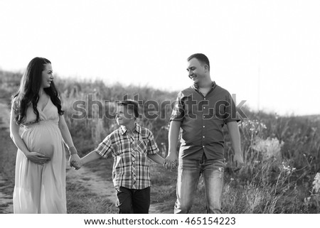 Family. Family Portrait. Young happy family walking outdoor. Pregnant woman, husband and child - happy family having fun on nature. Young couple loves they child. Beautiful Family, lifestyle concept