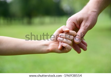 Family, father and child son hands over green summer nature outdoor. Trust and help concept. Toned. - stock photo