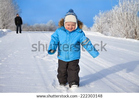 family, father and happy small child the boy on walk in the winter in park - stock photo