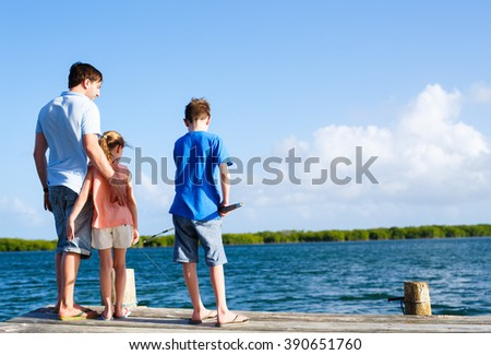 Family father and kids fishing together from wooden jetty