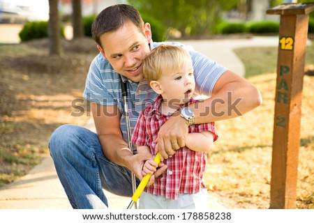 Family: Father Helps Little Boy With Putting At Mini-Golf - stock photo