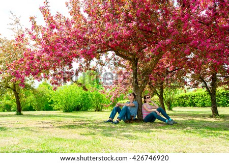 Family-father, teenage girl and small dog sitting under blossoming pink cherry tree in green park. Multicolored vibrant horizontal outdoors image. - stock photo