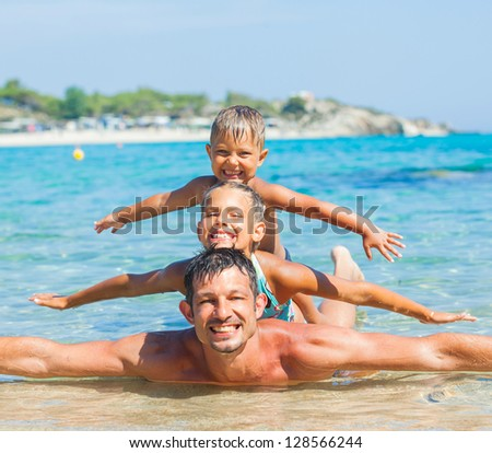 Family - father with his kids have fun and swim in the transparent sea - stock photo