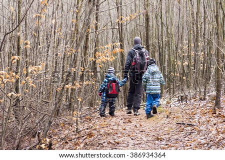 Family, father with two children hiking in forest in autumn or winter.  - stock photo