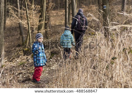 Family, father with two children hiking in forest in autumn or winter.