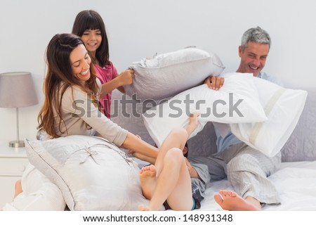 Family fighting together with pillows on bed at home - stock photo
