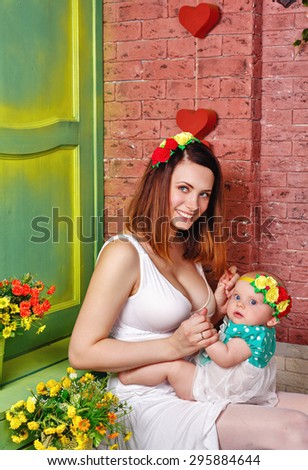 Family firstborn sits kneeling at his mother. The concept of a happy family. - stock photo