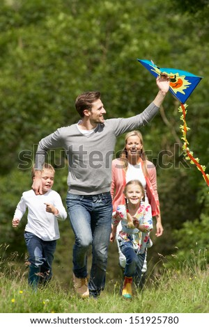 Family Flying Kite In Countryside - stock photo