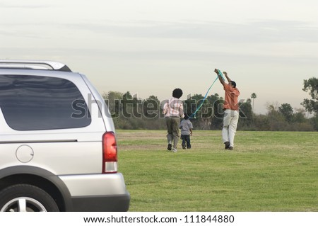 Family flying kite together in the park - stock photo