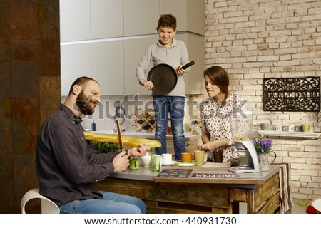 Family forming a band in kitchen, pretending to play on instruments. - stock photo