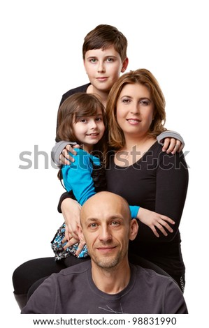 Family from four people, the father, mother, the daughter and the son with happy persons, embrace, are photographed on a white background in studio