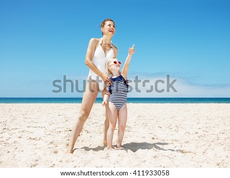 Family fun on white sand. Full length portraits of happy mother and child pointing to somewhere while standing at sandy beach on a sunny day - stock photo
