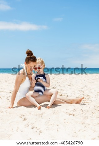 Family fun on white sand. Happy mother and child in swimsuits at sandy beach on a sunny day looking on photos in digital camera - stock photo