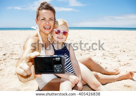 Family fun on white sand. Happy mother and child in swimsuits taking selfies with digital camera at sandy beach on a sunny day