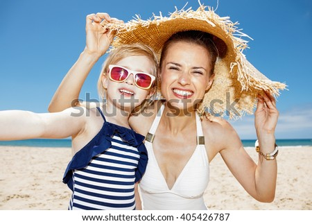Family fun on white sand. Happy mother and daughter under big straw hat taking selfie at sandy beach on a sunny day