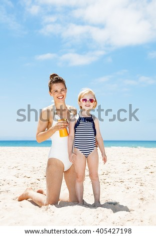 Family fun on white sand. Happy mother applying sunscreen on child in swimsuit at sandy beach on a sunny day