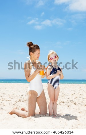 Family fun on white sand. Happy mother applying sunscreen on girl in swimsuit at sandy beach on a sunny day - stock photo