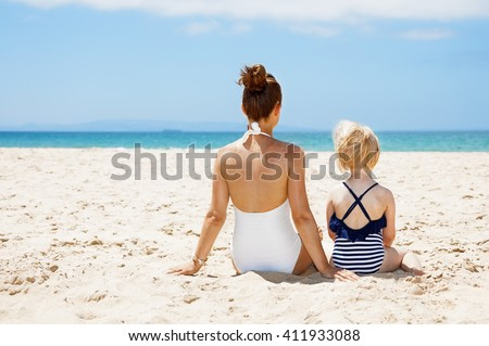 Family fun on white sand. Seen from behind mother and child in swimsuits sitting at sandy beach on a sunny day - stock photo