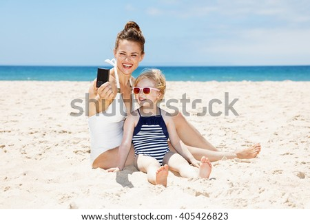 Family fun on white sand. Smiling mother and daughter in swimsuits taking selfies with digital camera at sandy beach on a sunny day