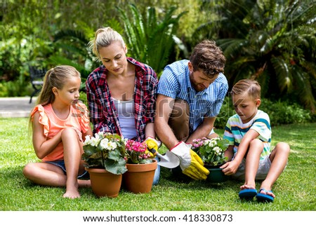 Family gardening with flower pots sitting on grass at yard