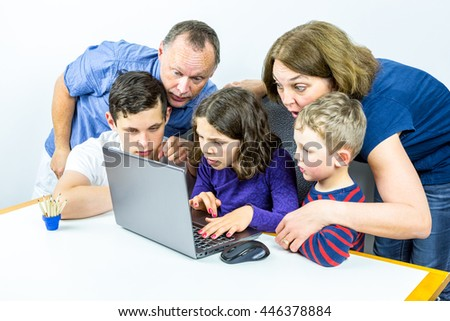 Family gathered around laptop looks at shocking content on internet together, studio shot