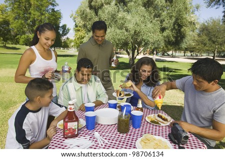 Family Gathered Around Picnic Table - stock photo