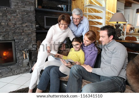 Family gathered together looking at photographs - stock photo