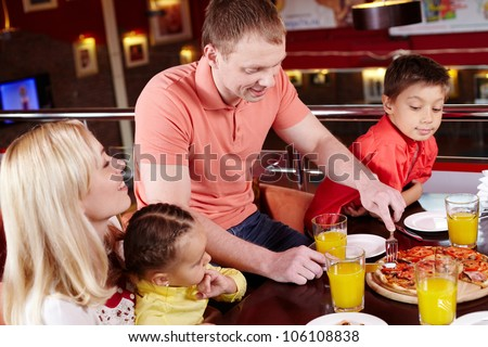 Family gathered together to enjoy pizza at the local pizzeria - stock photo