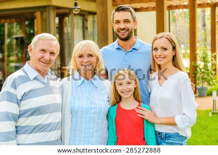 Family gathering. Happy family of five people bonding to each other and smiling while standing at the back yard of their house together  - stock photo
