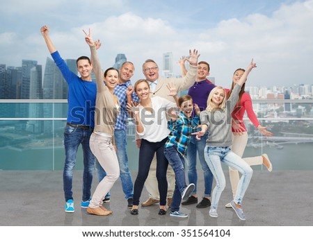 family, gender, generation and people concept - group of happy men, women and boy having fun and waving hands over singapore city waterside background - stock photo