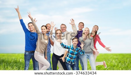 family, gender, generation and people concept - group of smiling men, women and boy having fun and waving hands over blue sky and grass background - stock photo
