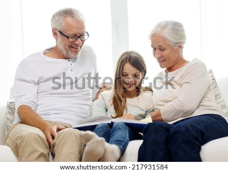 family, generation and people concept - smiling grandfather, granddaughter and grandmother with book sitting on couch at home - stock photo