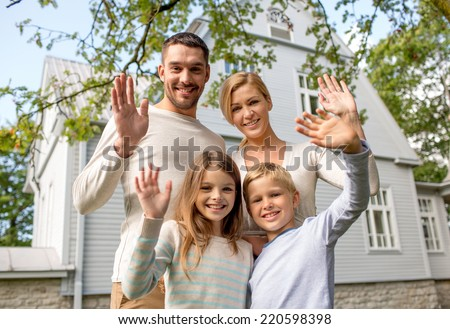family, generation, home, gesture and people concept - happy family standing in front of house waving hands outdoors - stock photo