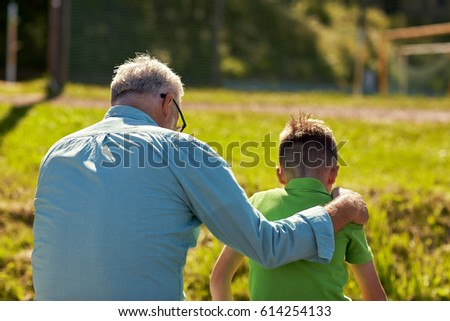 family, generation, relations and people concept - grandfather and grandson hugging outdoors