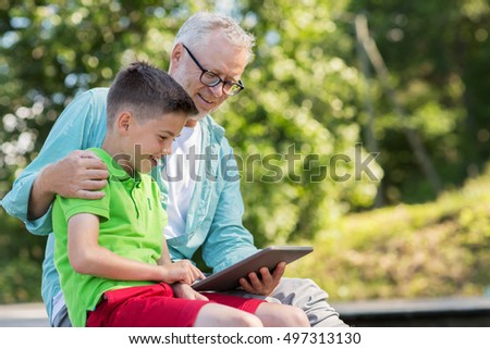 family, generation, technology, communication and people concept - happy grandfather and grandson with tablet pc computer outdoors