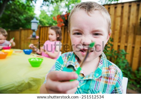 Family getting ready to color Easter eggs.  A smiling boy holds a green paint brush waiting to paint and decorate some Eggs during the spring season in a garden setting.  Part of a series. - stock photo